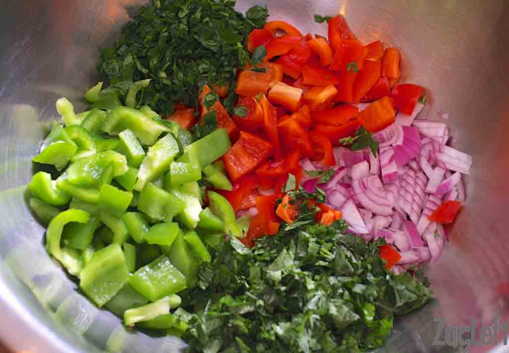 Chopped green and red bell peppers, chopped red onion, chopped parsley, and chopped cilantro in a large metal mixing bowl