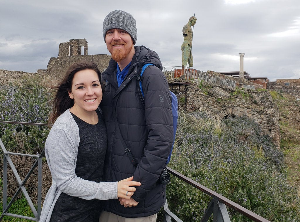 posing for couple photo with pompeii ruins in Italy behind us