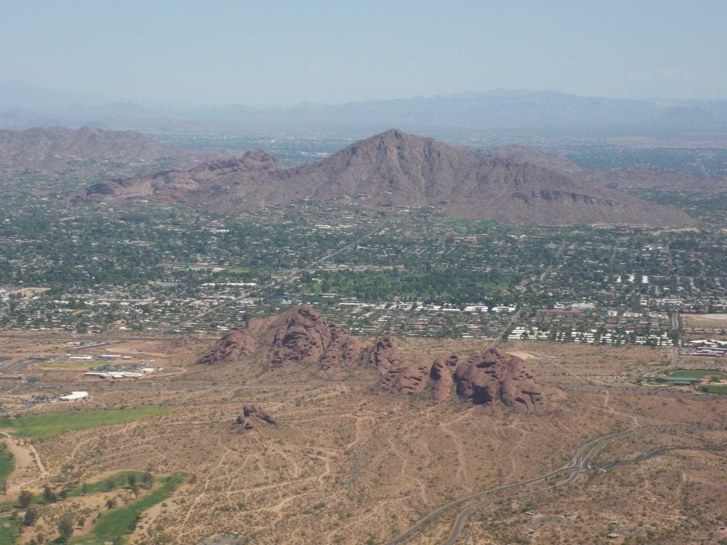 camelback mountain is dark red in coloe an is in the shape of a sleeping camel