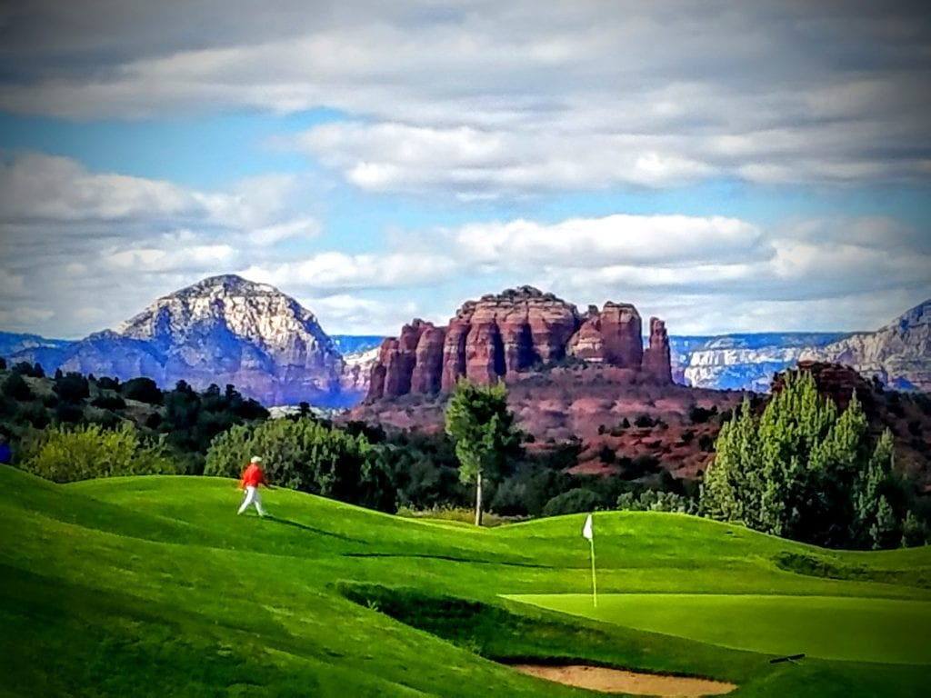 golfer on course with sedona red rocks in view