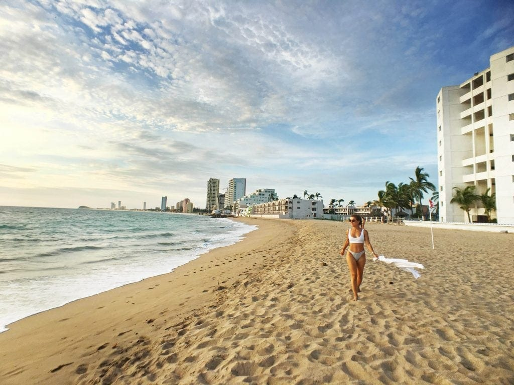 woman walks on sunny beach in Mazatlan