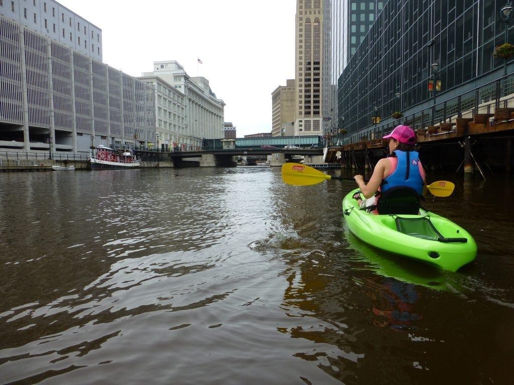 Kayaker looks at Milwaukee skyscrapers while urban kayaking