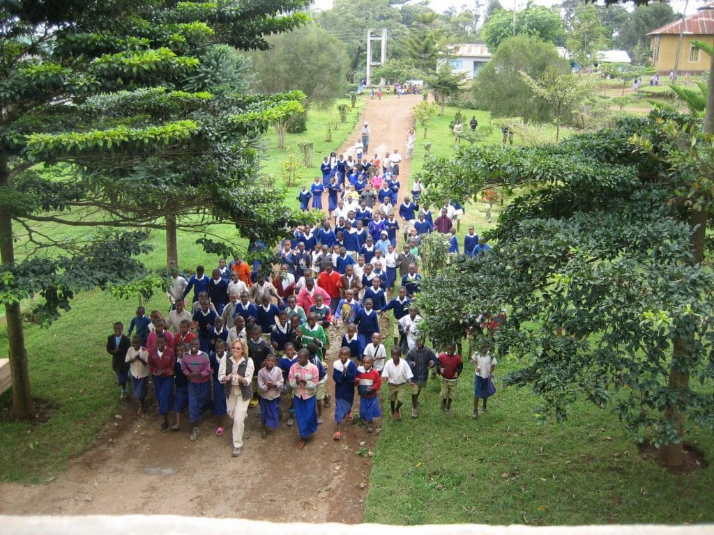 Shot from overhead of author leading over 60 African children into a church for Bible study time.