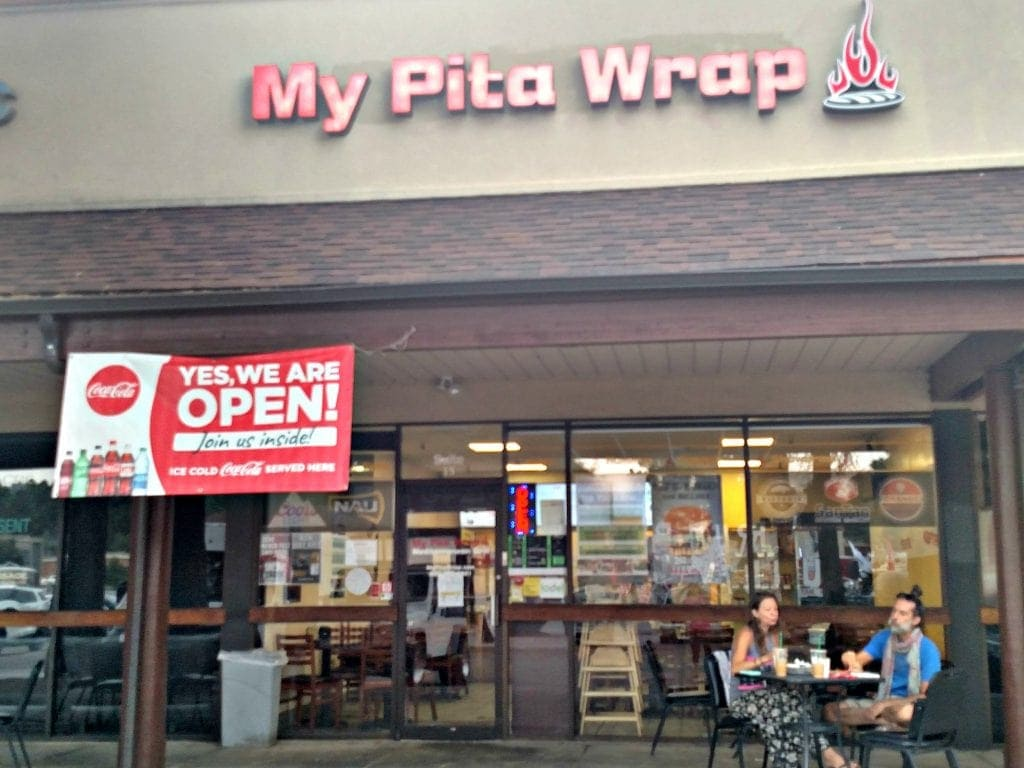 "Front of restaurant with banner that reads ""We're open"" at one of the best places to eat in Flagstaff AZ"