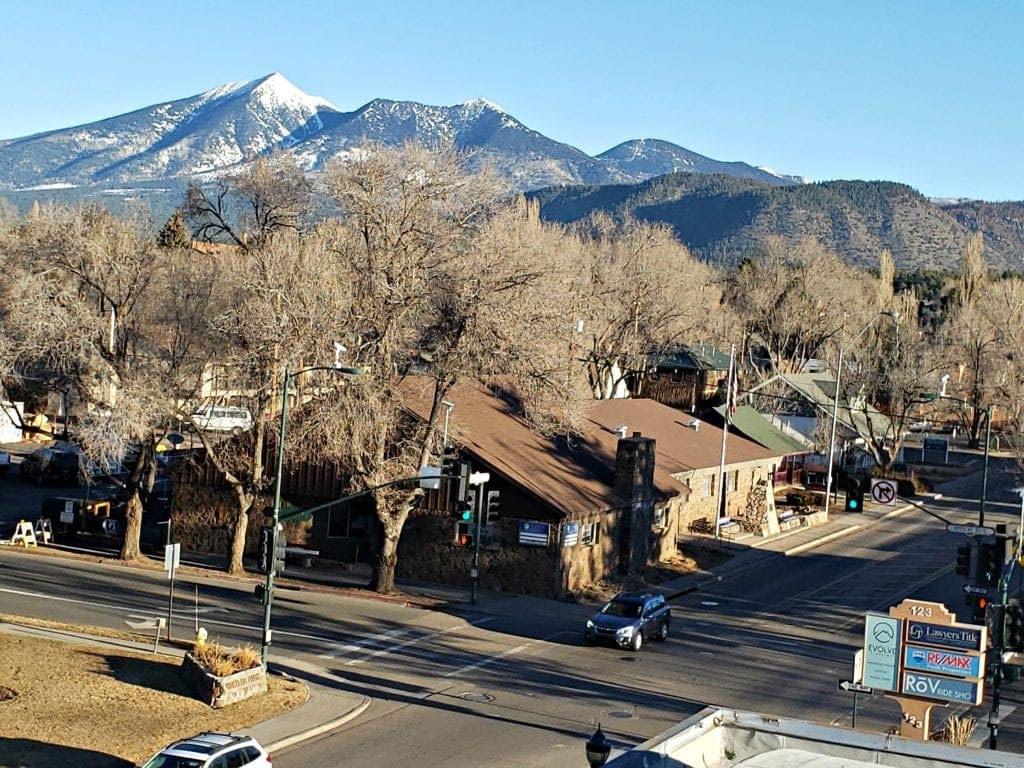 Snow-topped SAn frnacisoc Peaks seen over tree tops in downtown Flagstaff