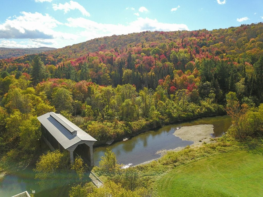 Drone shot of a covered bridge going over a river and surrounded by bright and colorful trees in vermont during fall