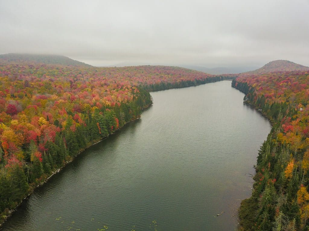 Drone shot of a large lake on a gloomy day surrounded by colorful trees in Groton State Forest