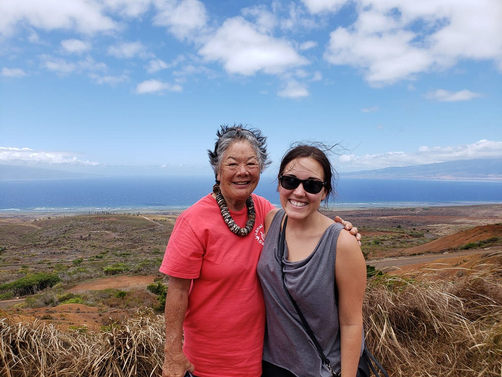 photo with tour guide on lanai tour with island views behind