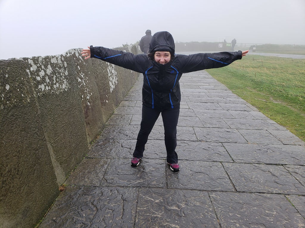 Brooke leaning into the wind during our windy, rainy and foggy adventure to the Cliffs of Moher