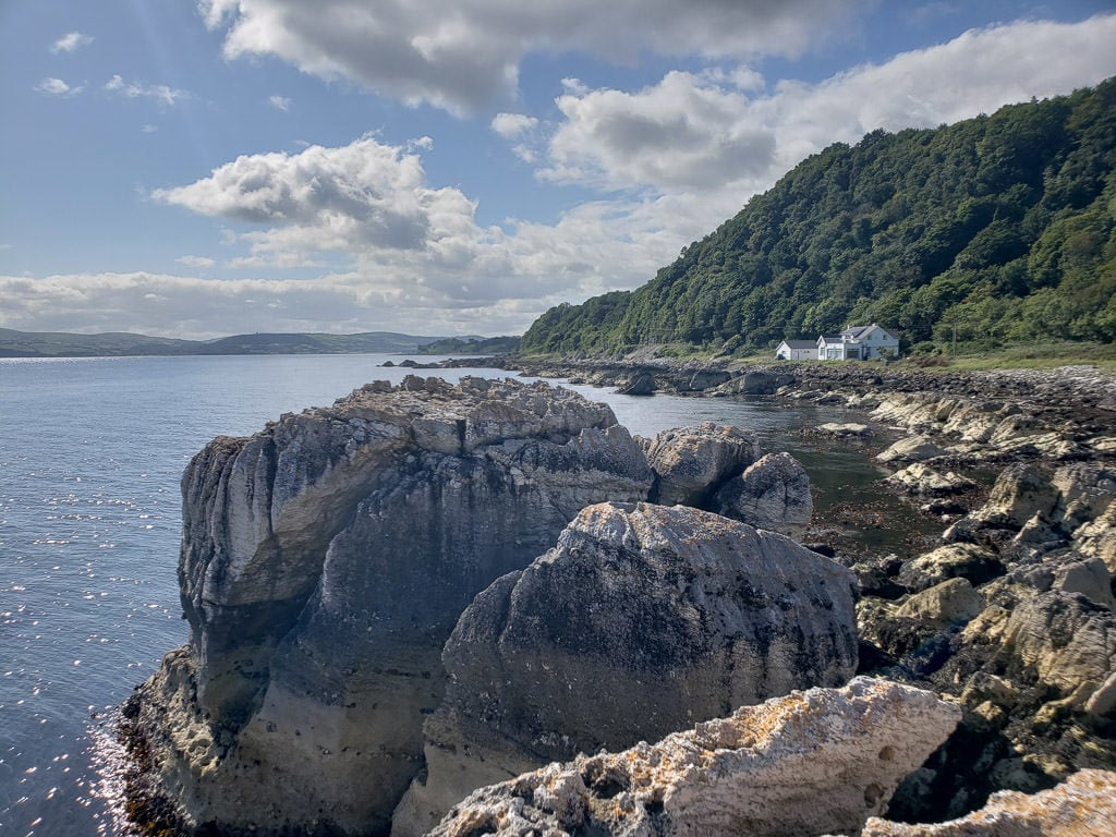 Rocky coast of Northern Ireland with tree covered hills