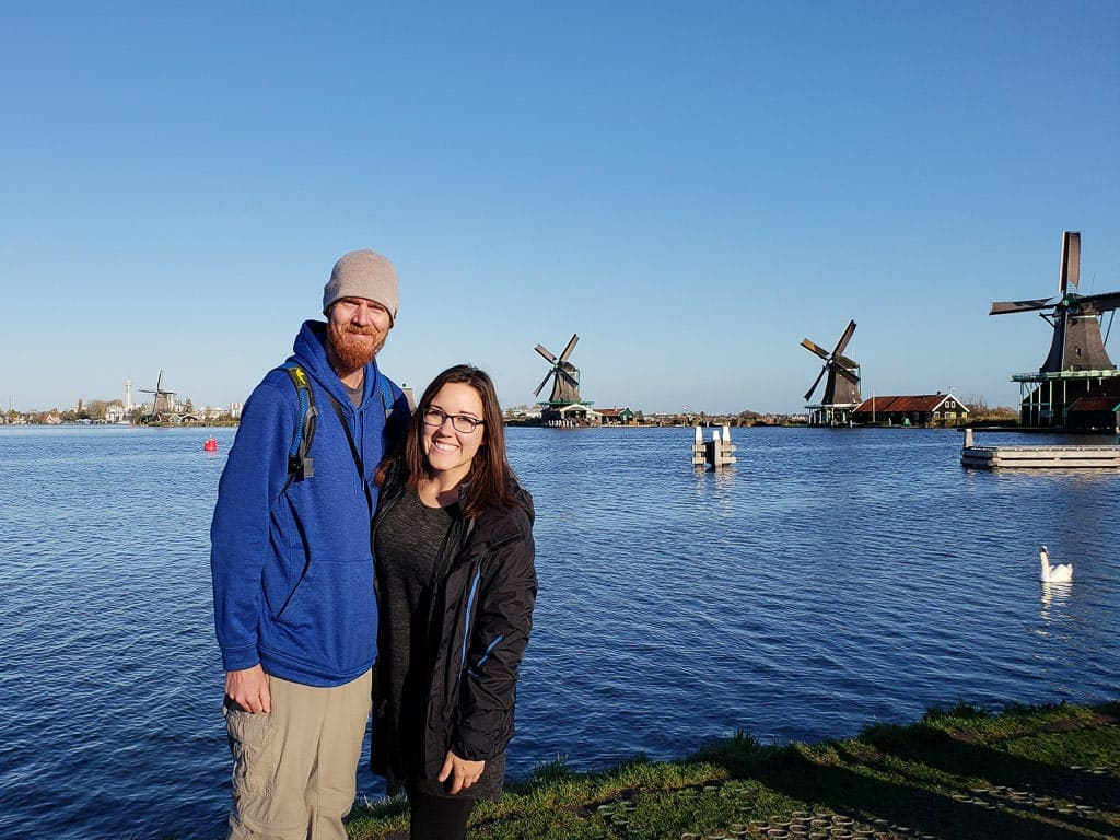 standing in front of windmills in zaane schans on day trip from amsterdam to holland's countryside