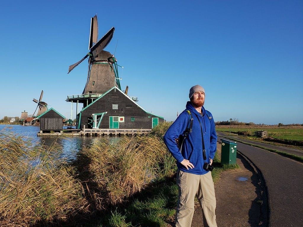 posing in front of windmill in zaane schans on day trips from amsterdam to holland's countryside
