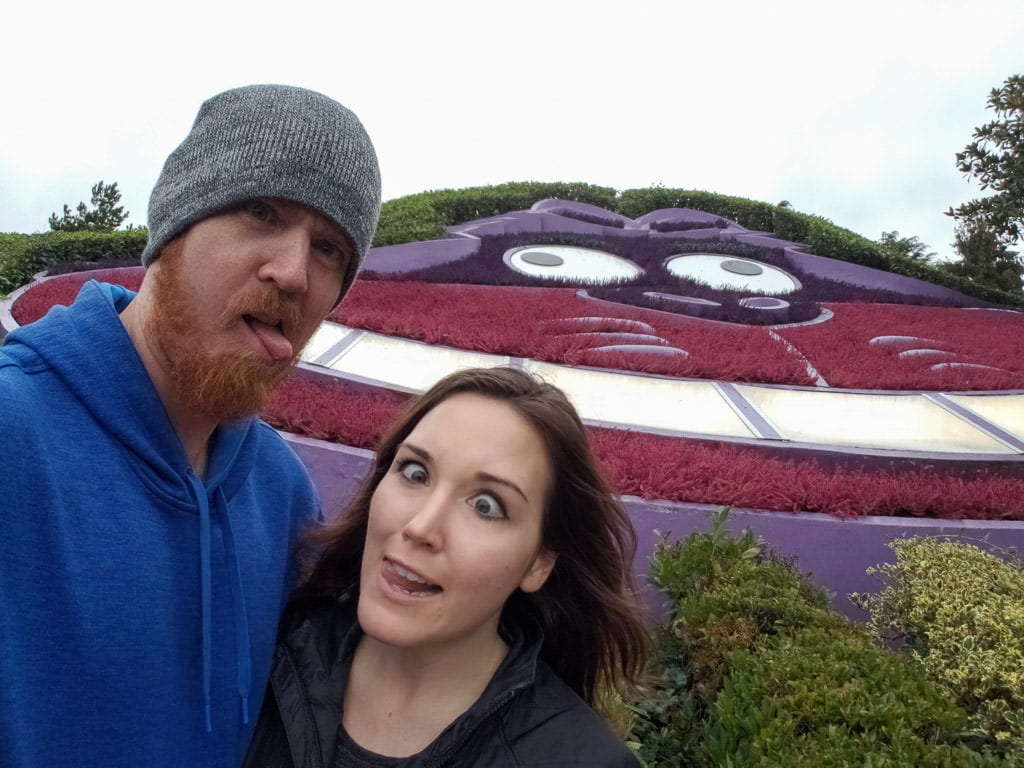 Brooke and Buddy making funny faces in front of the Cheshire Cat flower garden in the Alice in Wonderland area of disneyland paris