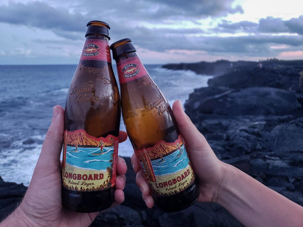 uncle roberts night market pahoa hawaii with beers at the rocky beach at sunset