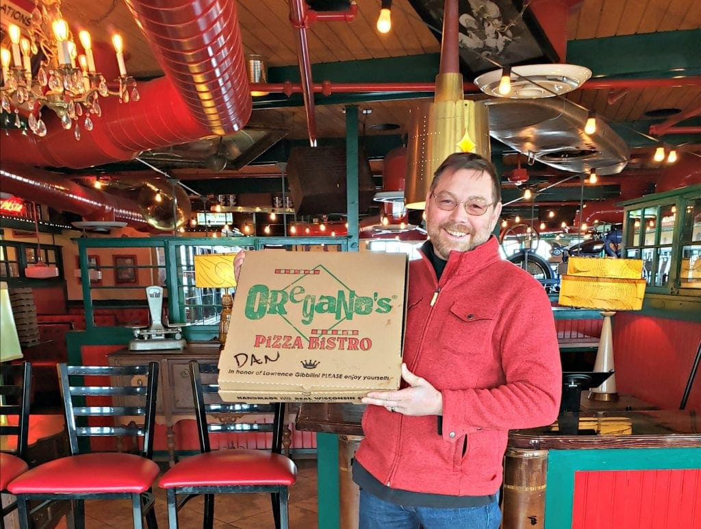Man holds pizza box to camera - restarant filled with fun memoriabilia in background makes this one of the best restaurants in Flagstaff