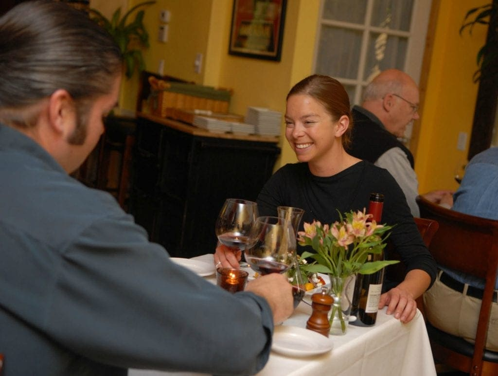 two people sit at table with white linen drinking red wine