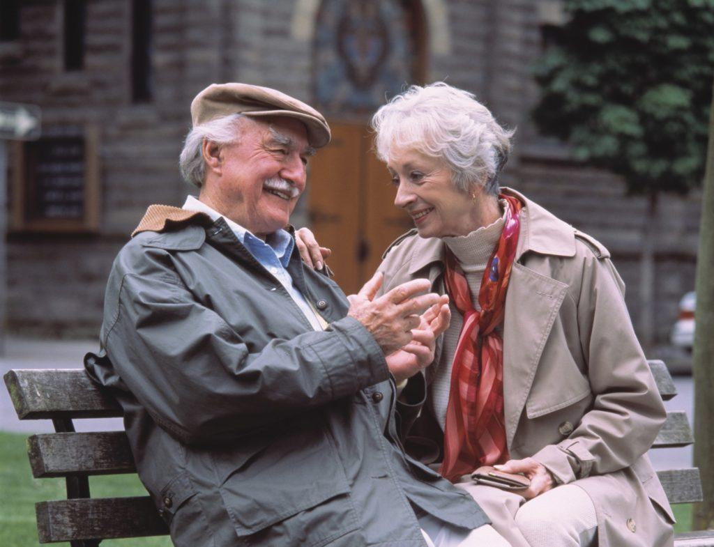 Old Couple sitting on bench enjoying their pension