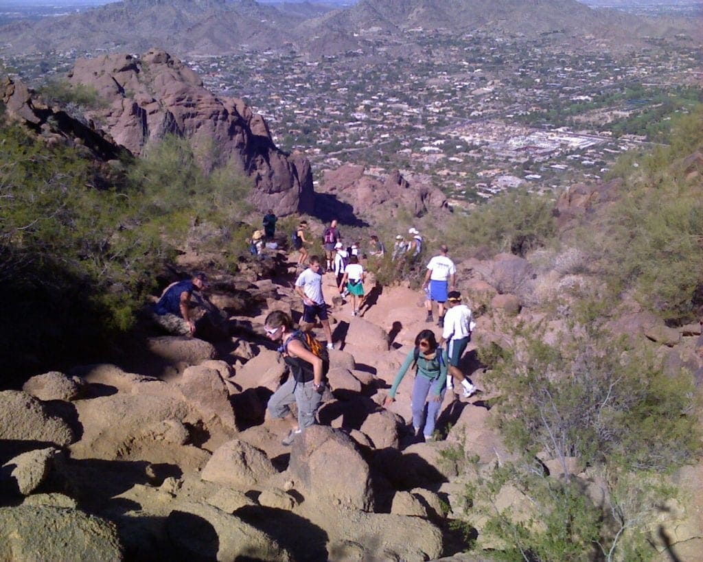 hikers climbing up boulder firled near top of Camelback Mountain