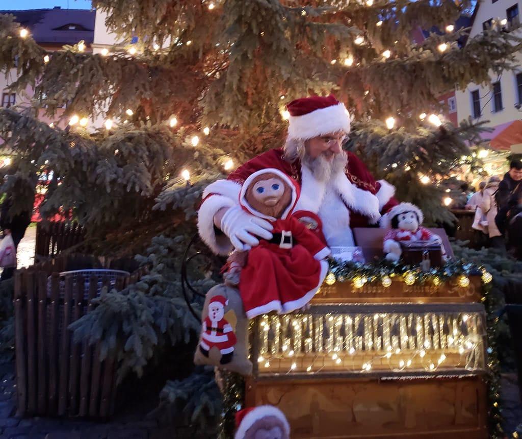 santa hand-cranking music at christmas market in rothenburg germany