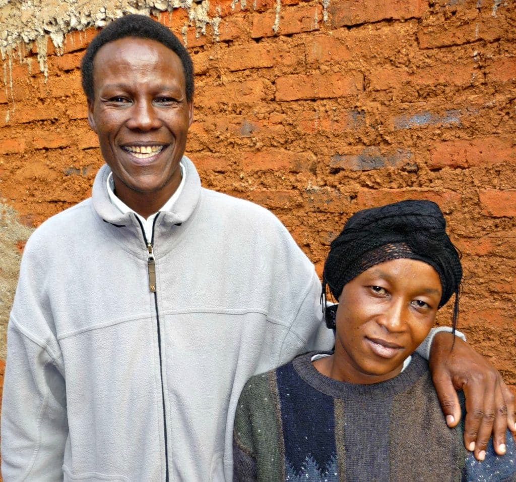 Tall man stands next to his wife whose head is wrapped in the Tanzanian style with his hand on her shoulder