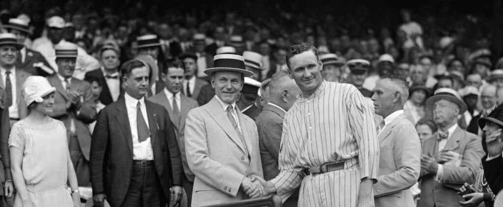 US President Calvin Coolidge (left) and Washington Senators pitcher Walter Johnson (right) shake hands.