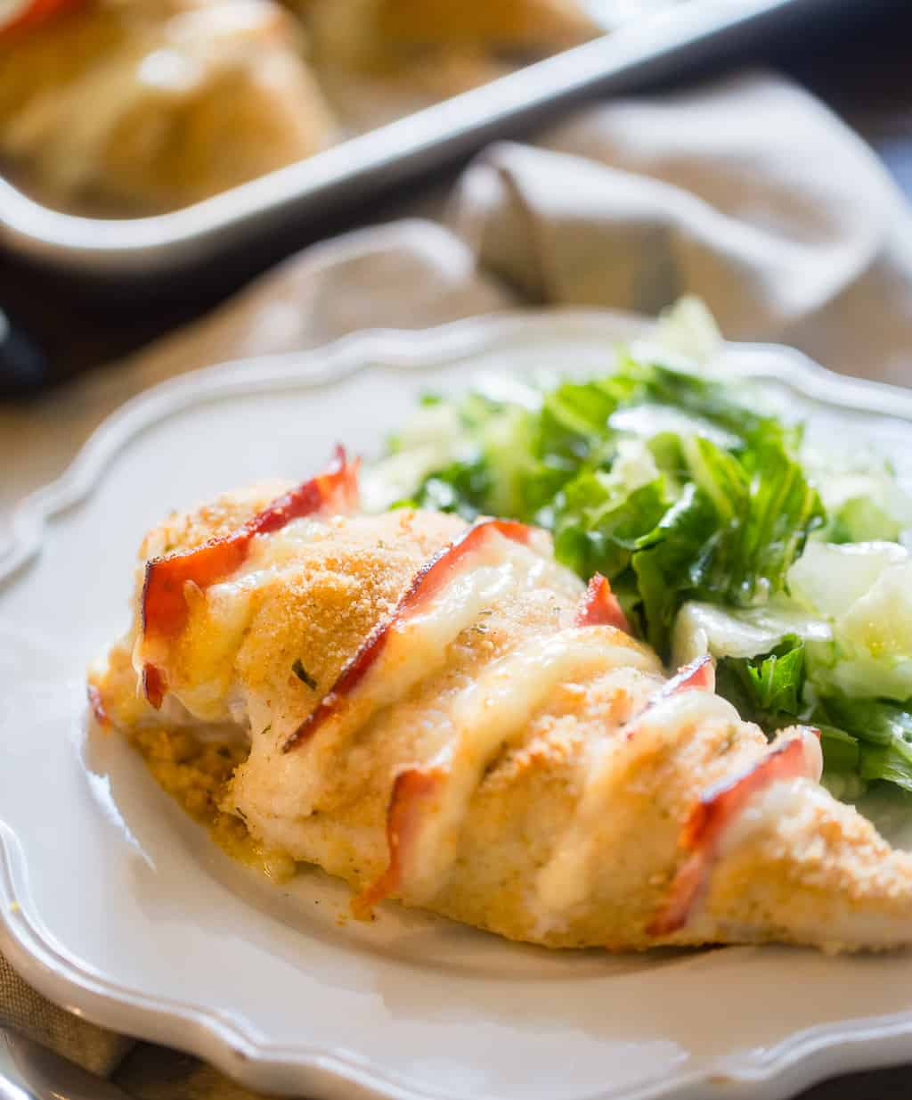Baked Chicken Cordon Bleu on a plate with side salad