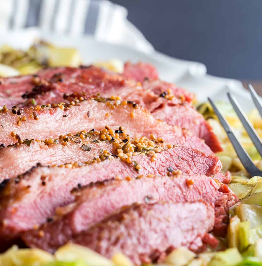 close up of baked corned beef recipe sliced on cabbage