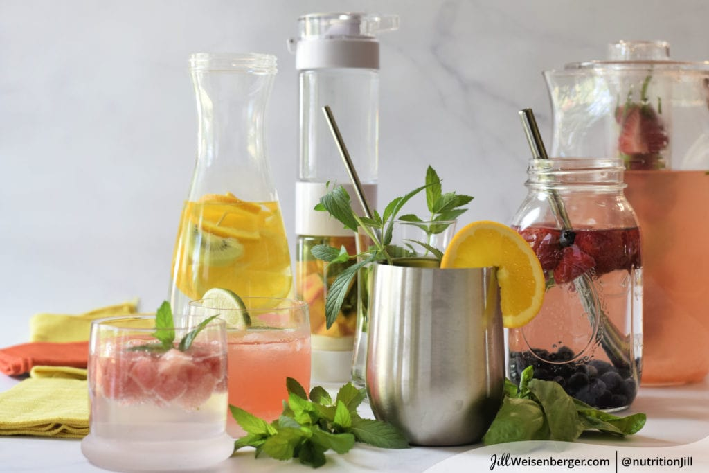 Glasses and pitchers with water, fruit and herbs to flavor water naturally