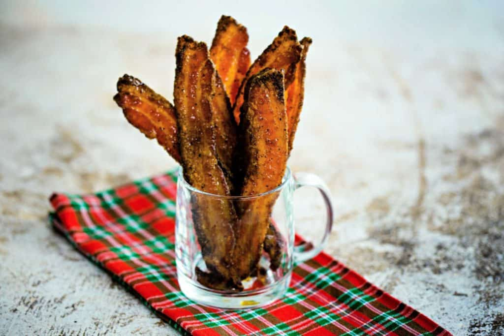 slices of sugared pepper bacon in a clear glass mug