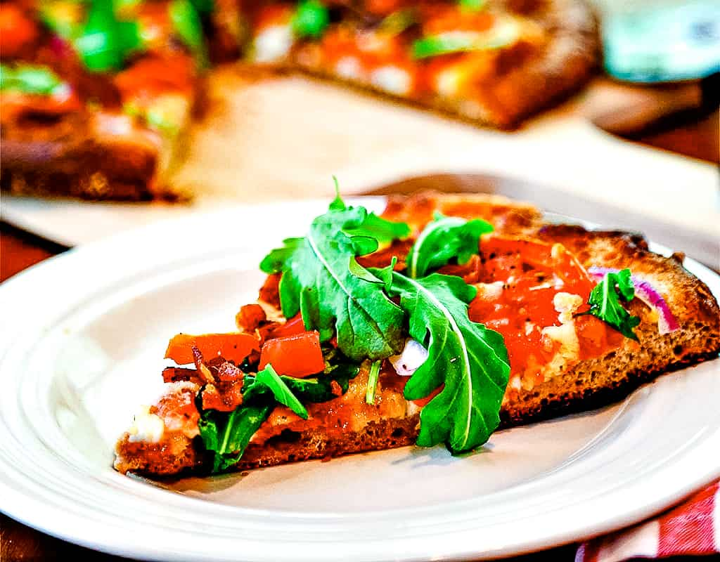Slice of BLT pizza on a white plate