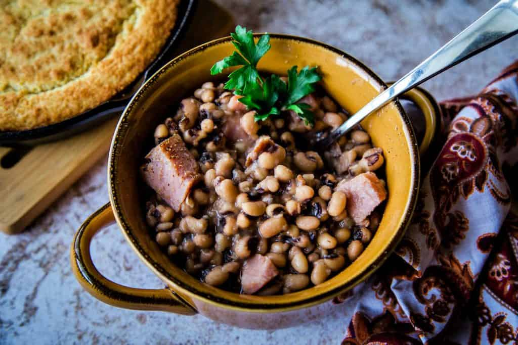a bowl of black eyed peas with chunks of ham and a skillet of cornbread