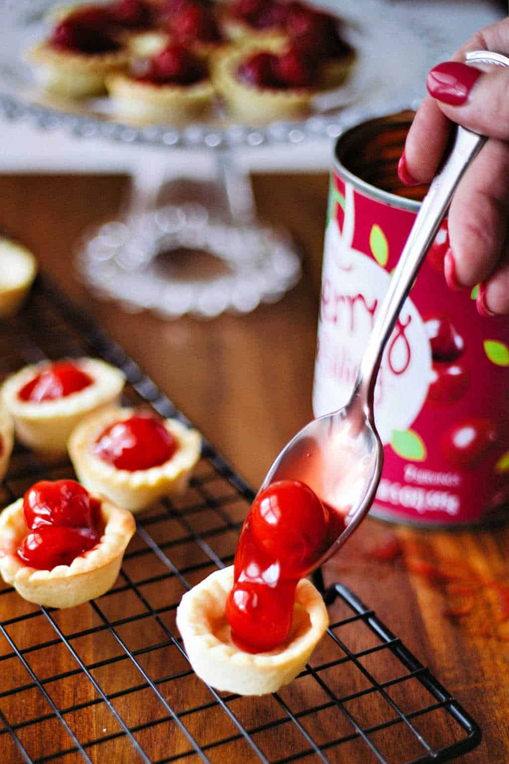 filling a miniature tart shell with canned cherry pie filling