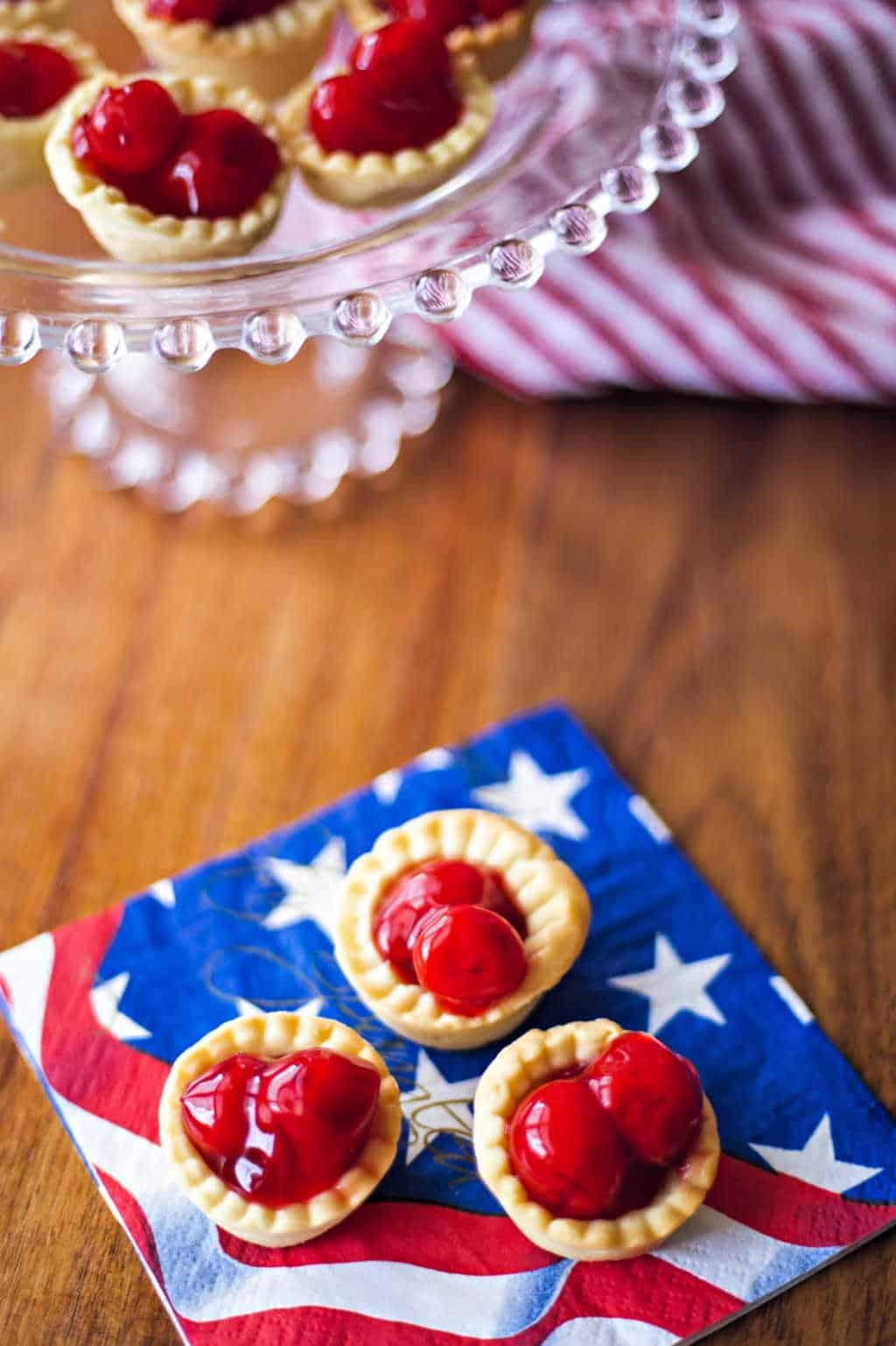 3 bite size cherry tarts on a patriotic napkin