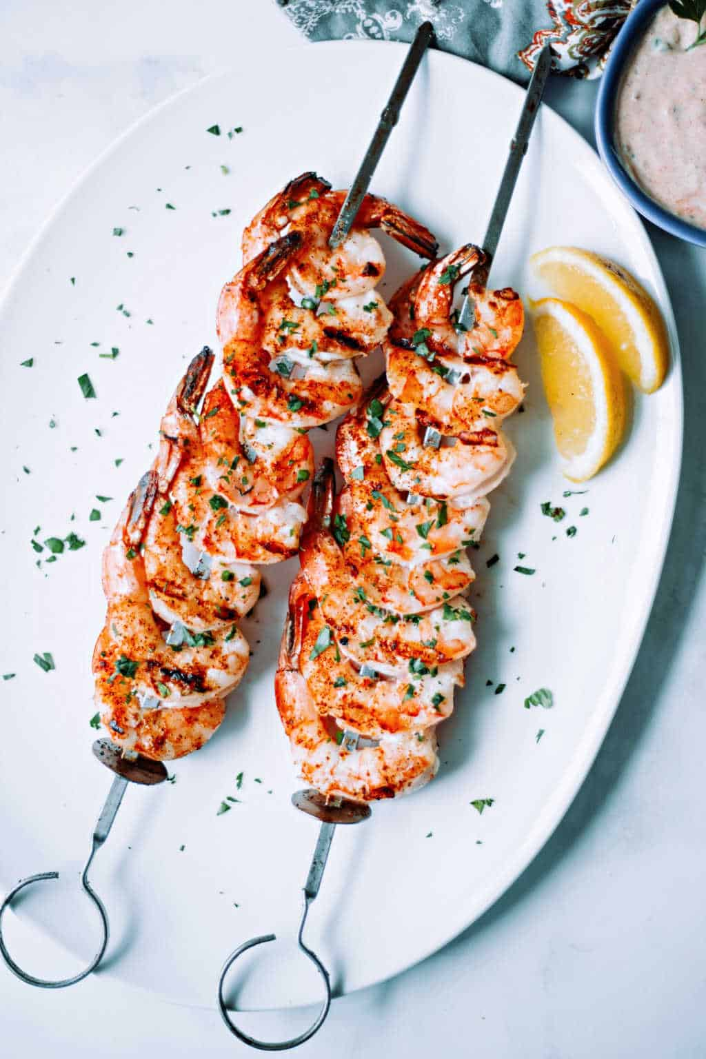 shrimp on the barbie skewers on a white platter with lemon wedges and parsley