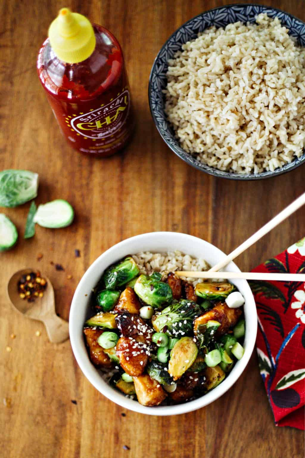 Sriracha Chicken and Brussels Sprouts Stir Fry in a white bowl with chopsticks and a bowl of rice
