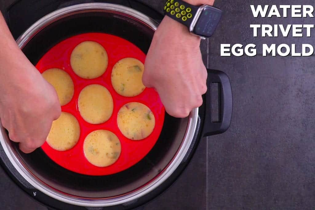 """Add water, metal trivet, and filled egg bites mold into instant pot. Cook on """"steam"""" setting for 8 minutes."""