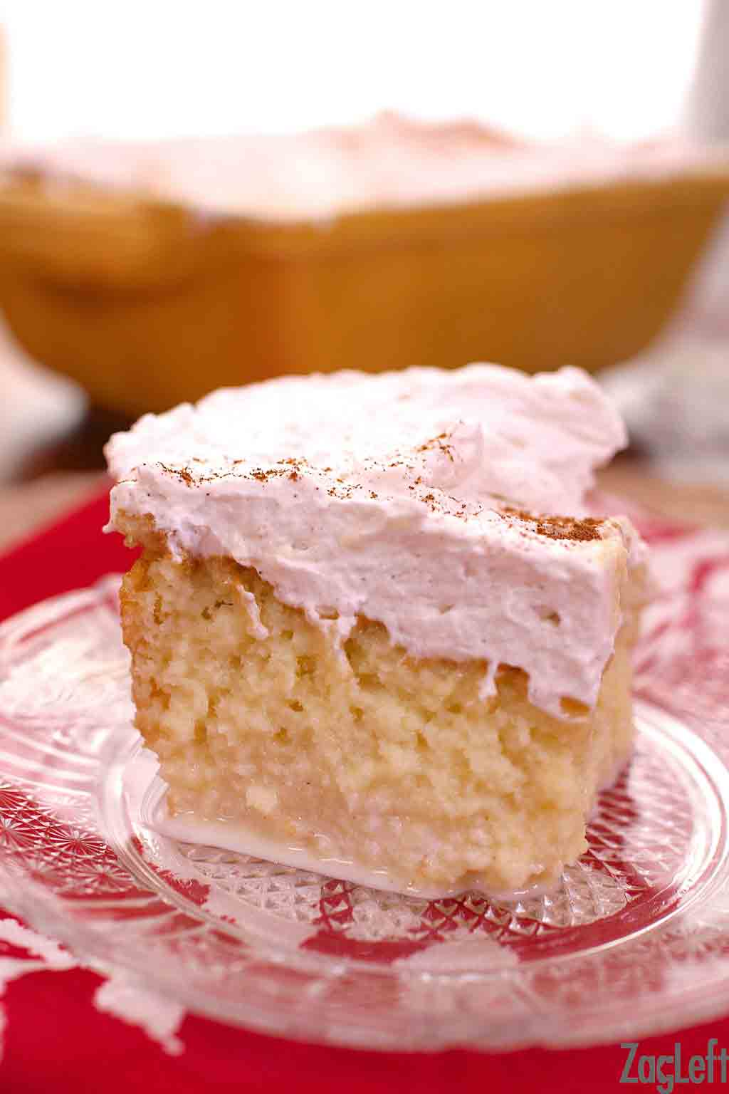 A square slice of tres leches cake on a plate.