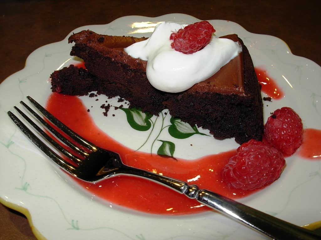 Homemade Raspberry Sauce garnishes this lovely Flourless Chocolate Cake.