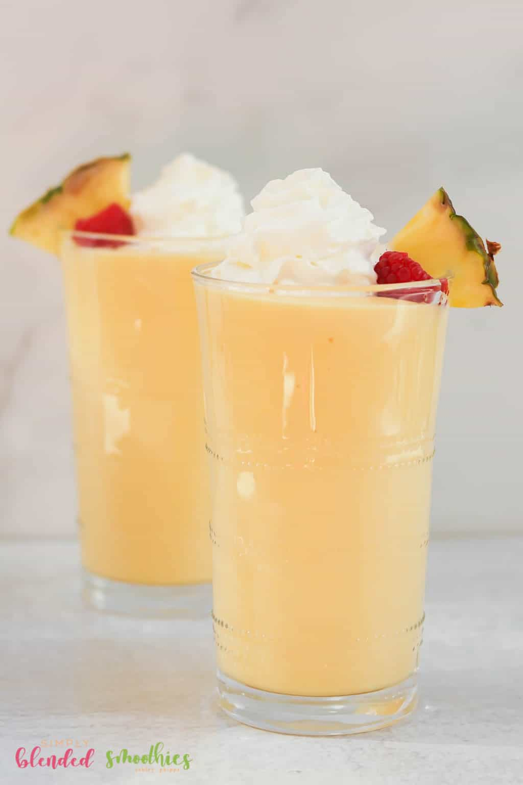 vertical photo of two pineapple peach milkshakes topped with a pineapple slice raspberry and whipped cream