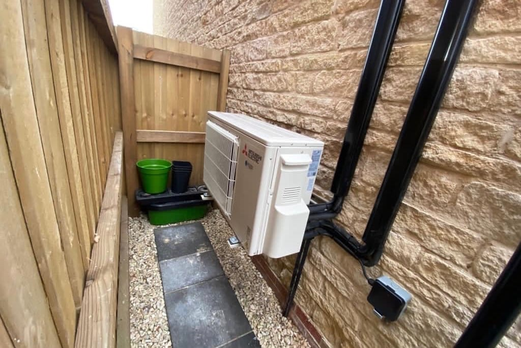 Mitsubishi Electirc external unit on side of house by path to garden with black piping
