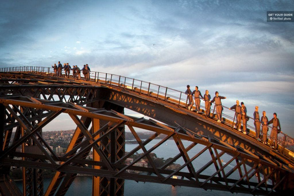 group walking up Sydney Harbor Bridge at golden hour