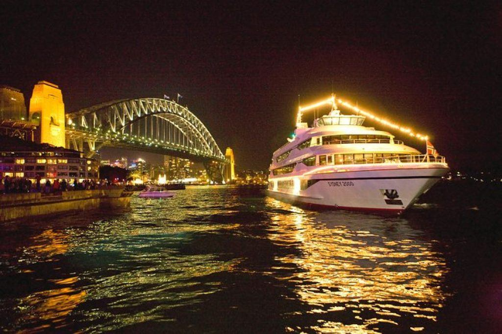 Sydney harbour dinner cruise boat on the water surrounded with lights and reflections