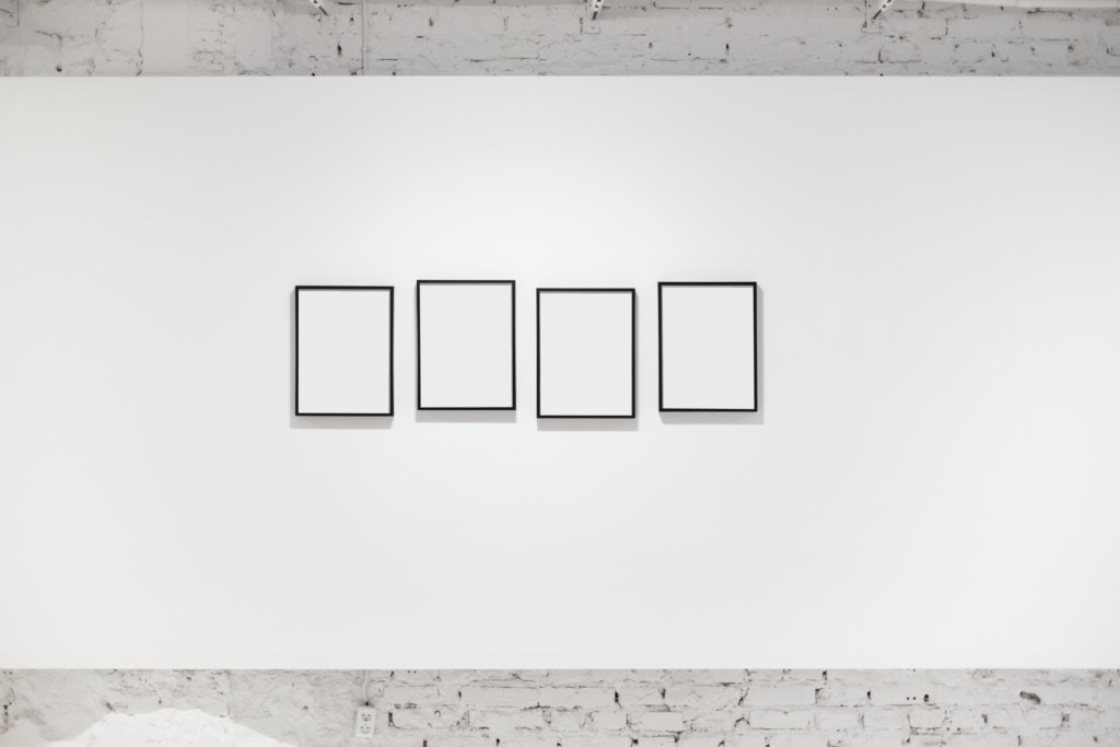 A white wall with four empty photo frames