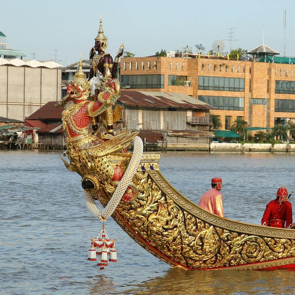 Four armed god - one face dark, the other red faced with gilded wings in the water for the Royal Barge Processional.