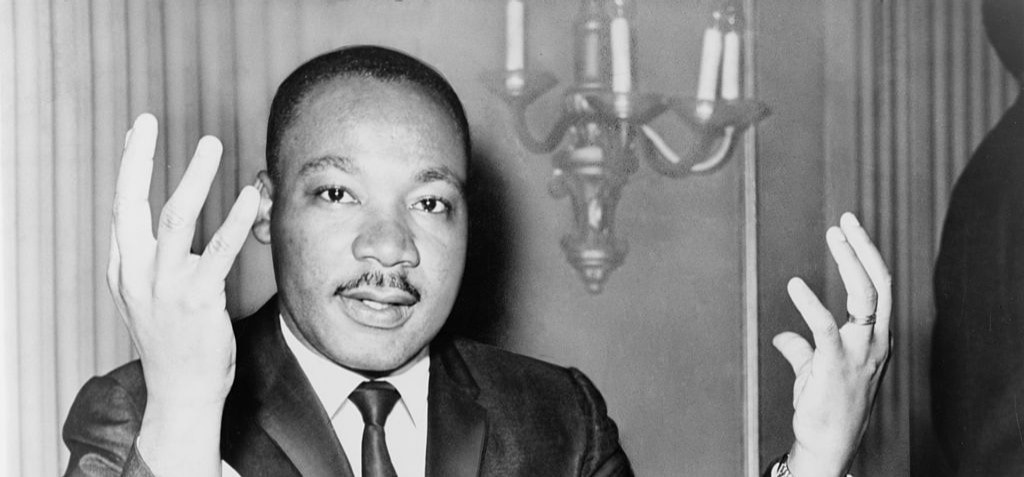 Civil rights leader and pastor Martin Luther King, Jr holds up both hands as he sits