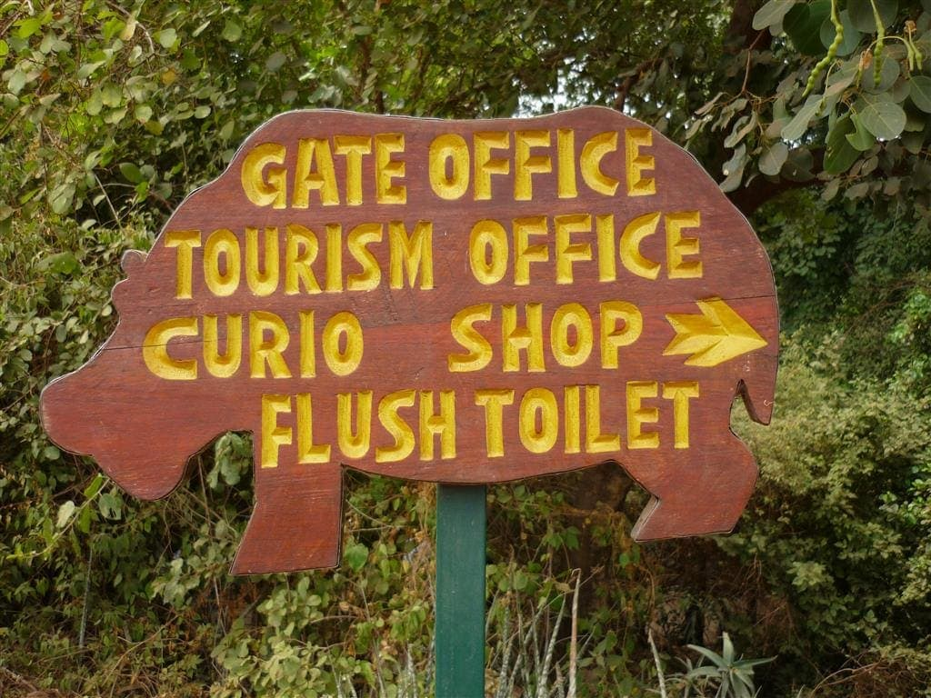 """wooden sign cut in the shape of a hippo says """"Gate Office, Tourism Office, Curio shop and Flush Toilet at Manyara wildlife safari camp park headquarters"""