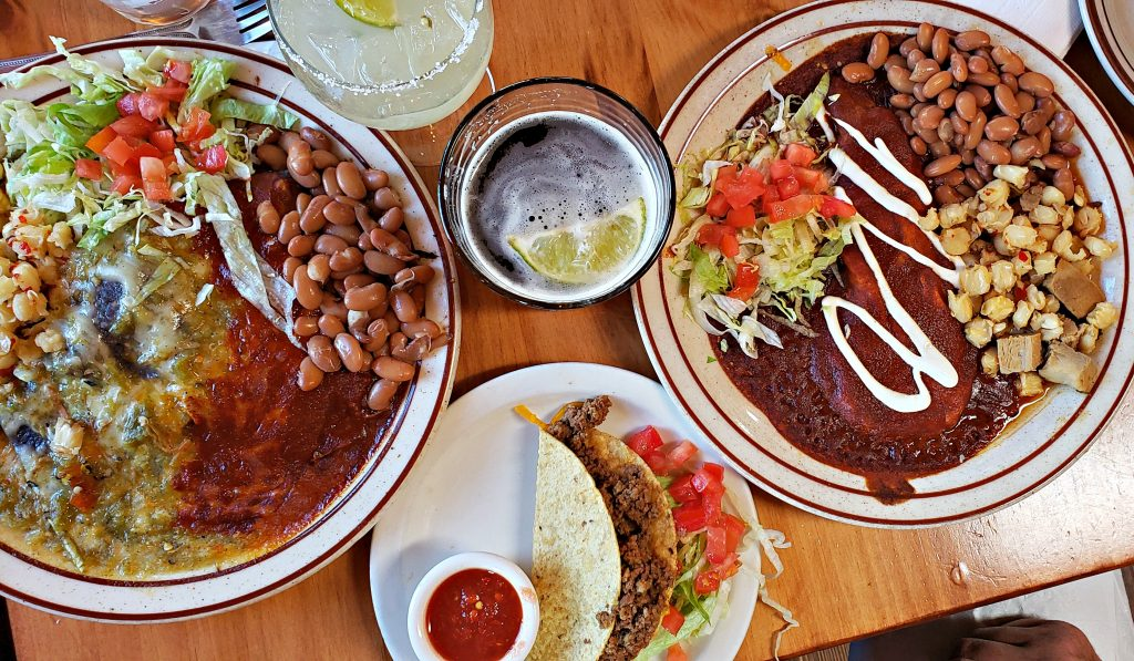 Plates of New Mexican cuisine sit on wood table - shot from above and includes a margarita, one of the best margaritas in santa fe