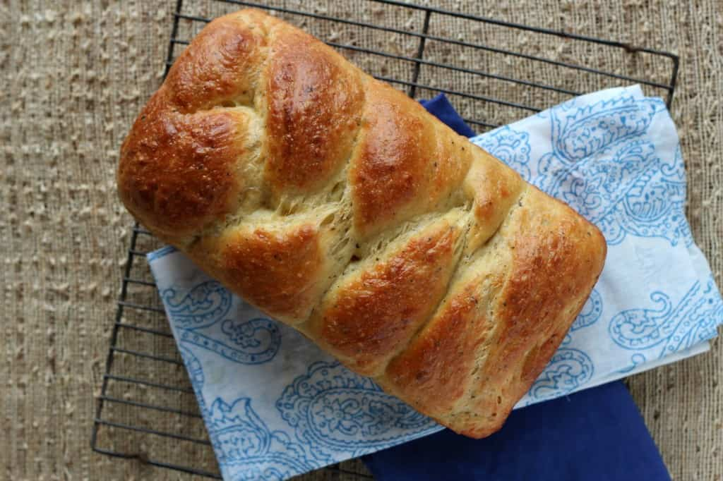 Italian Easter Bread on a wire cooling rack with blue printed napkin