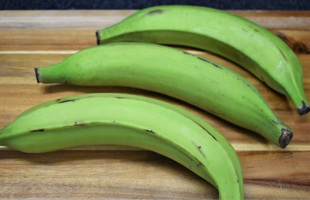 Green Plantains for tostones, uncut and arranged on a cutting board