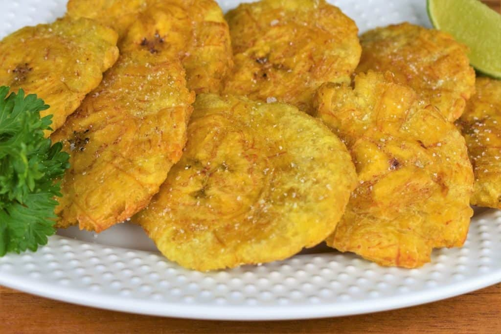 Tostones Flattened and Fried and arranged on a white plate